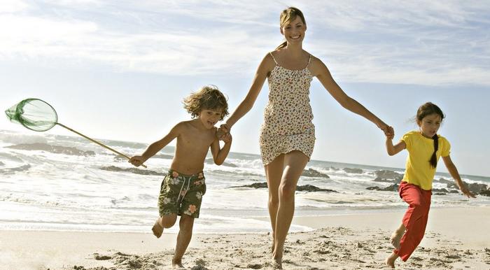 Женщина и дети на пляже