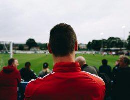 мужчина следит за футболом чтобы делать ставки на спорт