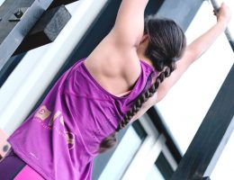 девушка подтягивается на брусьях фиолетовый