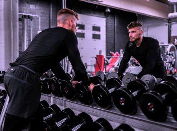 мужчина смотрит в зеркало в спортзале